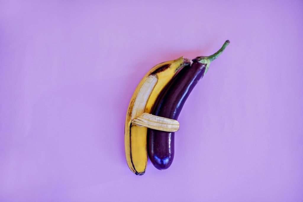 banana and eggplant on violet surface